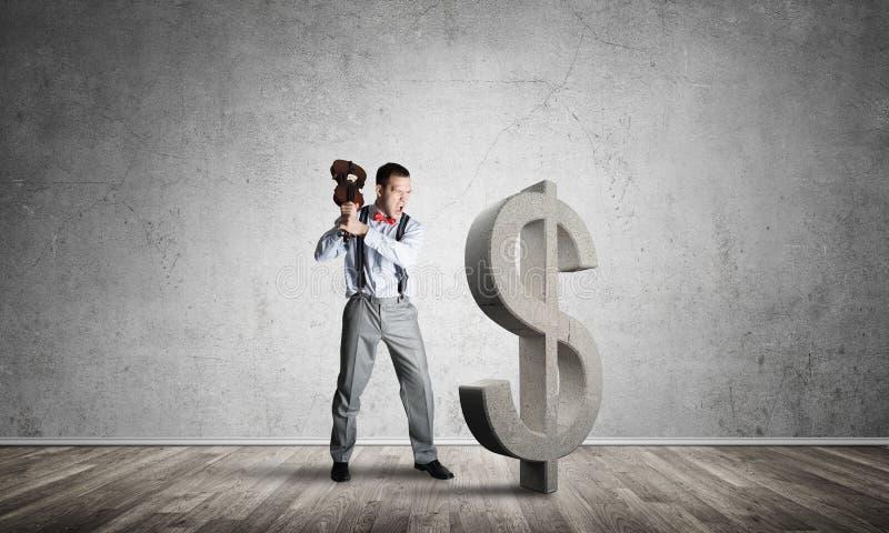 Homem determinado do banqueiro na sala concreta vazia que quebra a figura do dólar imagem de stock royalty free