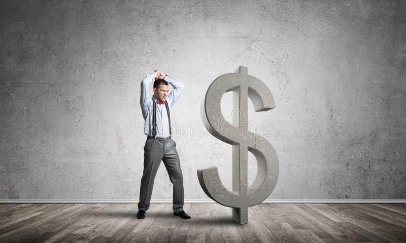 Homem determinado do banqueiro na sala concreta vazia que quebra a figura do dólar fotografia de stock royalty free