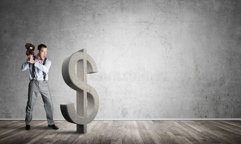 Homem determinado do banqueiro na sala concreta vazia que quebra a figura do dólar imagem de stock