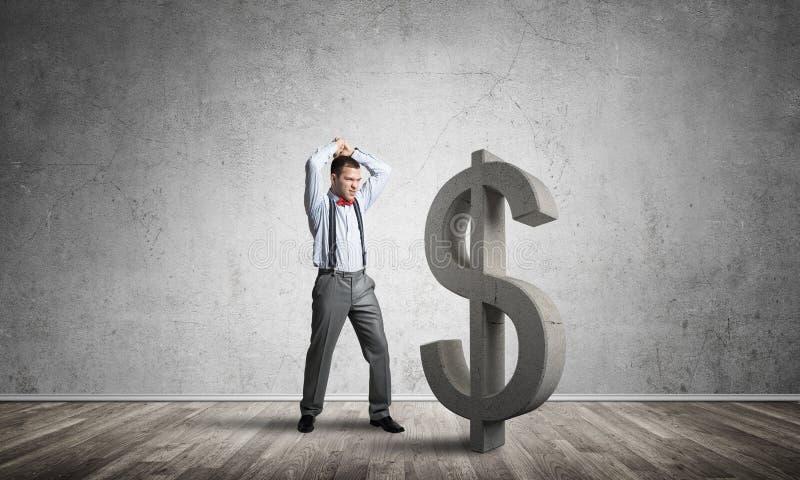 Homem determinado do banqueiro na sala concreta vazia que quebra a figura do dólar foto de stock royalty free