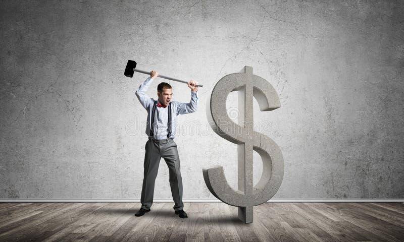 Homem determinado do banqueiro na sala concreta vazia que quebra a figura do dólar fotos de stock royalty free