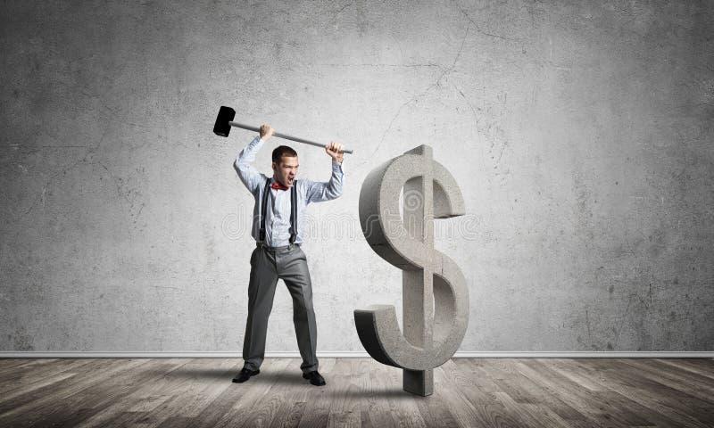 Homem determinado do banqueiro na sala concreta vazia que quebra a figura do dólar imagens de stock royalty free