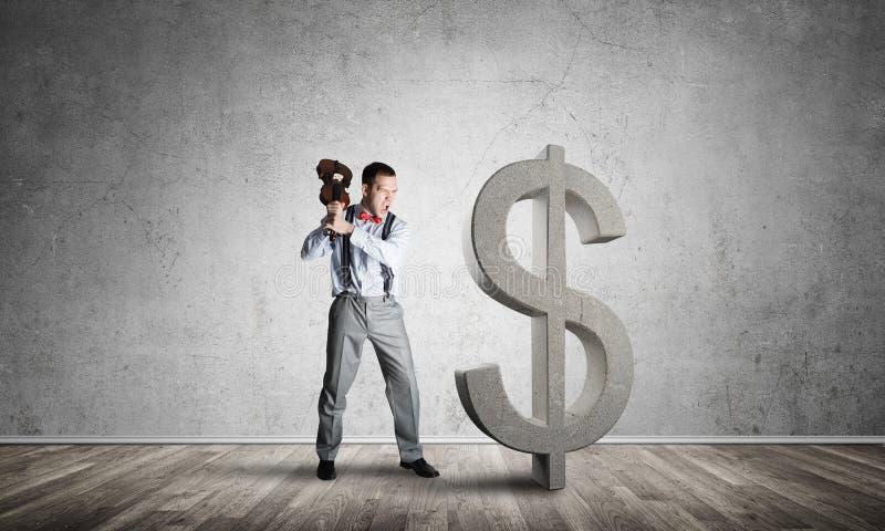 Homem determinado do banqueiro na sala concreta vazia que quebra a figura do dólar fotos de stock