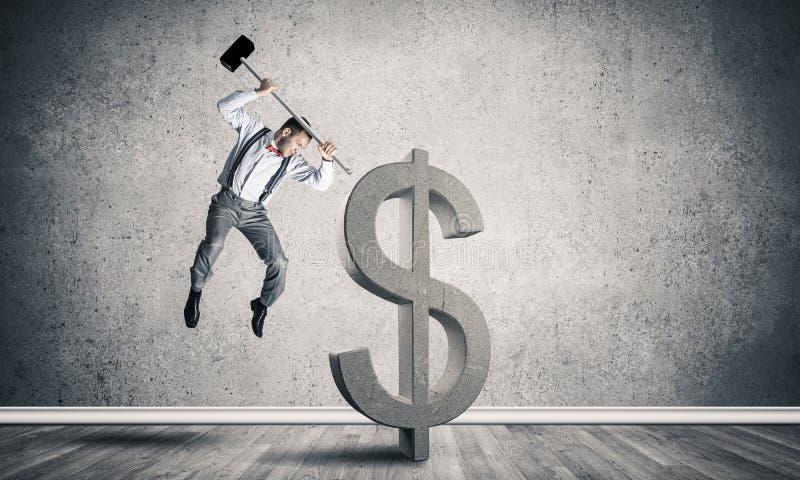 Homem determinado do banqueiro na sala concreta vazia que quebra o figo do dólar fotos de stock royalty free