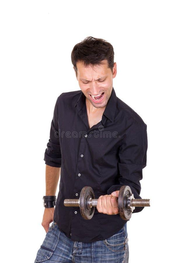 Homem determinado persistente em levantar peso preto da camisa fotografia de stock