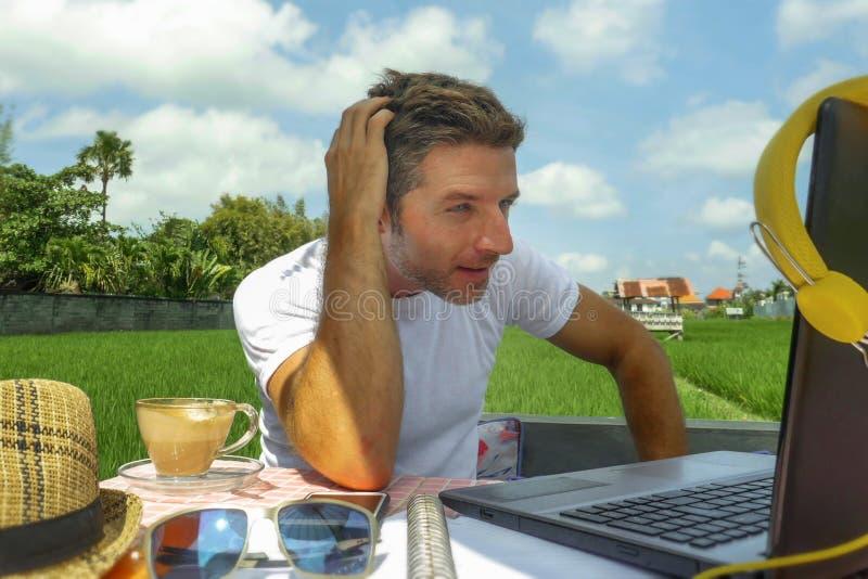 Homem digital atrativo novo do nômada que trabalha na linha fora com laptop e telefone celular como o freelancer e o jo independe fotos de stock