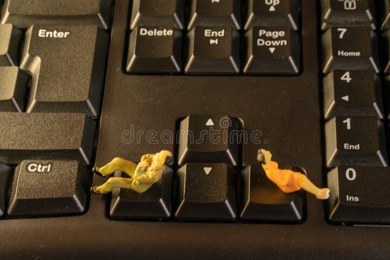 Homem diminuto e mulher que sentam-se no teclado de computador Conceito do divórcio do conflito da família foto de stock royalty free