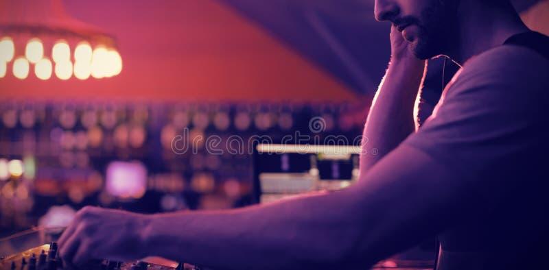 Homem DJ que escuta fones de ouvido ao jogar a música imagens de stock