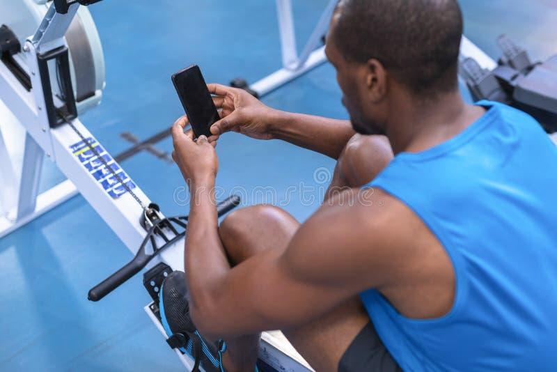 Homem do ajuste que usa o telefone celular ao exercitar na máquina de enfileiramento no fitness center fotografia de stock