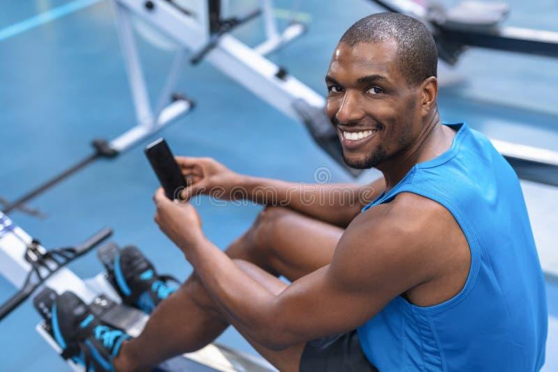 Homem do ajuste que usa o telefone celular ao exercitar na máquina de enfileiramento no fitness center imagem de stock royalty free
