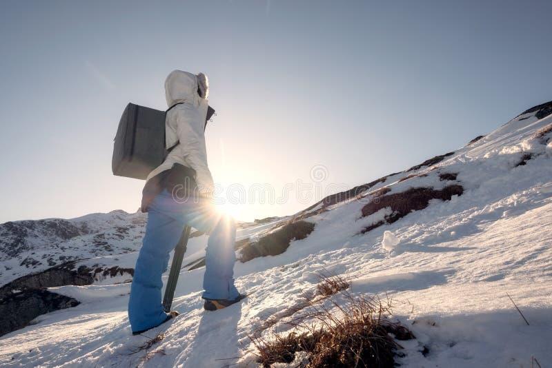Homem do alpinista que escala à montanha máxima no inverno no sunse foto de stock royalty free