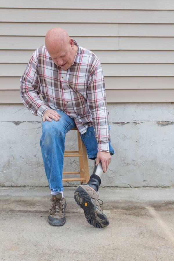 Homem do amputado que senta-se no tamborete que gira seu pé protético ao redor imagem de stock royalty free