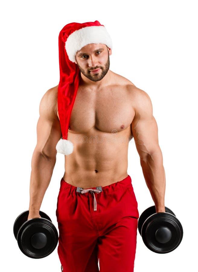 Homem do ano novo com corpo muscular no chapéu de Santa do vermelho e do White Christmas que está no estúdio com fundo branco fotografia de stock