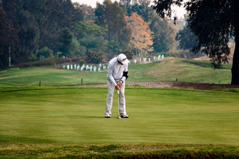 Homem do aposentado que põe sobre o verde golfing fotos de stock