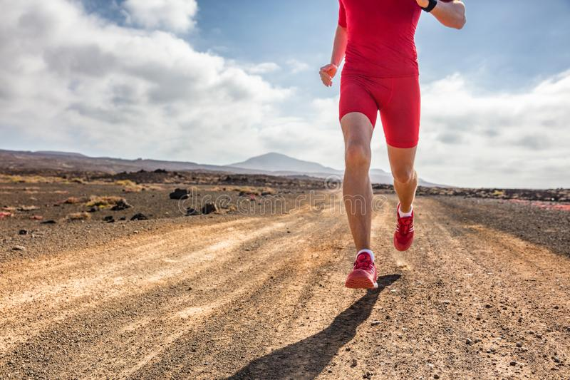 Homem do atleta do corredor da fuga que corre no trajeto da montanha da sujeira na roupa vermelha equipamento e tênis de corrida  fotos de stock royalty free