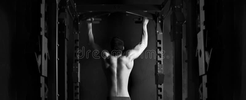 Homem do atleta do músculo no gym que faz elevações fotos de stock