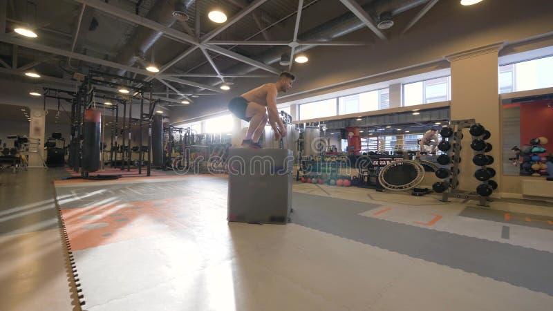 Homem do atleta que salta na plataforma no treinamento do crossfit no movimento lento de clube de aptidão fotos de stock royalty free