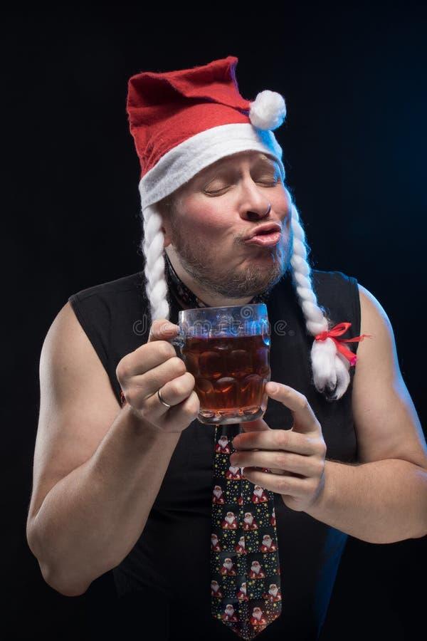 Homem do ator cômico no tampão com tranças com um vidro da cerveja, em antecipação ao Natal e ao ano novo foto de stock royalty free