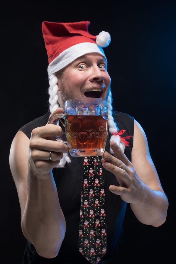 Homem do ator cômico no tampão com tranças com um vidro da cerveja, em antecipação ao Natal e ao ano novo fotos de stock royalty free