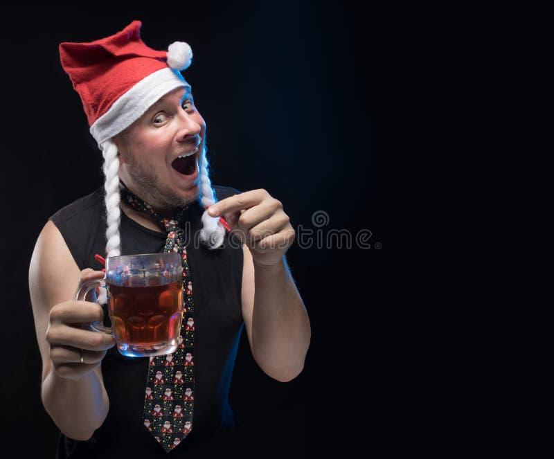 Homem do ator cômico no tampão com tranças com um vidro da cerveja, em antecipação ao Natal e ao ano novo imagem de stock royalty free