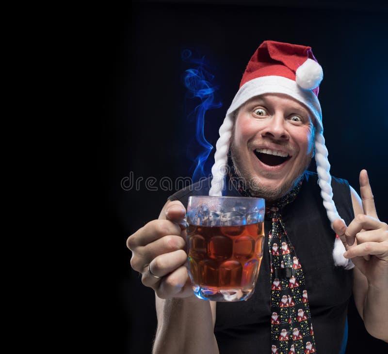 Homem do ator cômico no tampão com tranças com um vidro da cerveja, em antecipação ao Natal e ao ano novo fotografia de stock royalty free