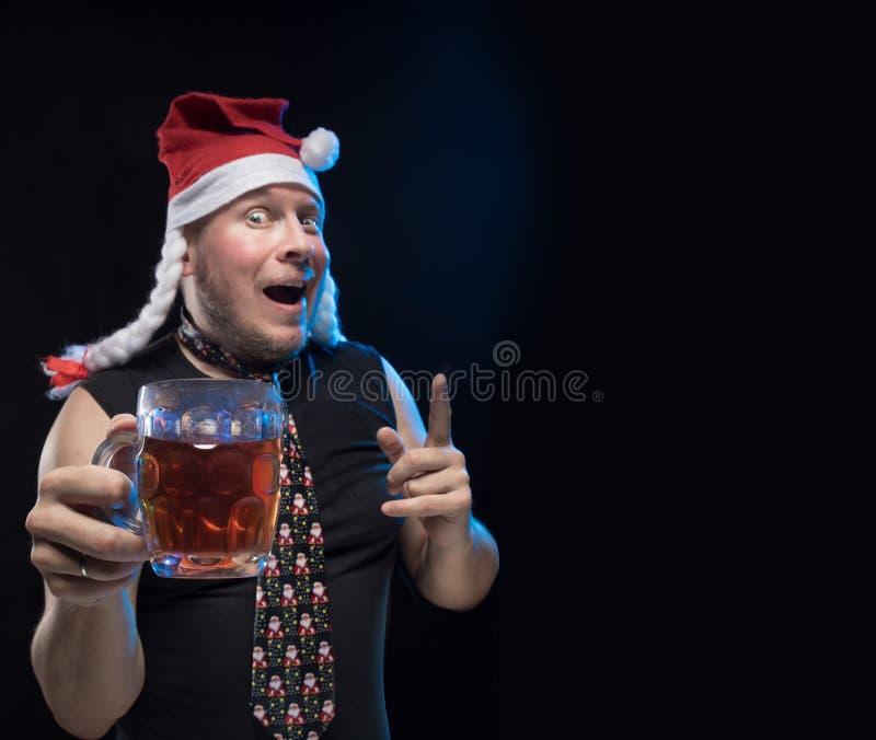 Homem do ator cômico no tampão com tranças com um vidro da cerveja, em antecipação ao Natal e ao ano novo fotos de stock