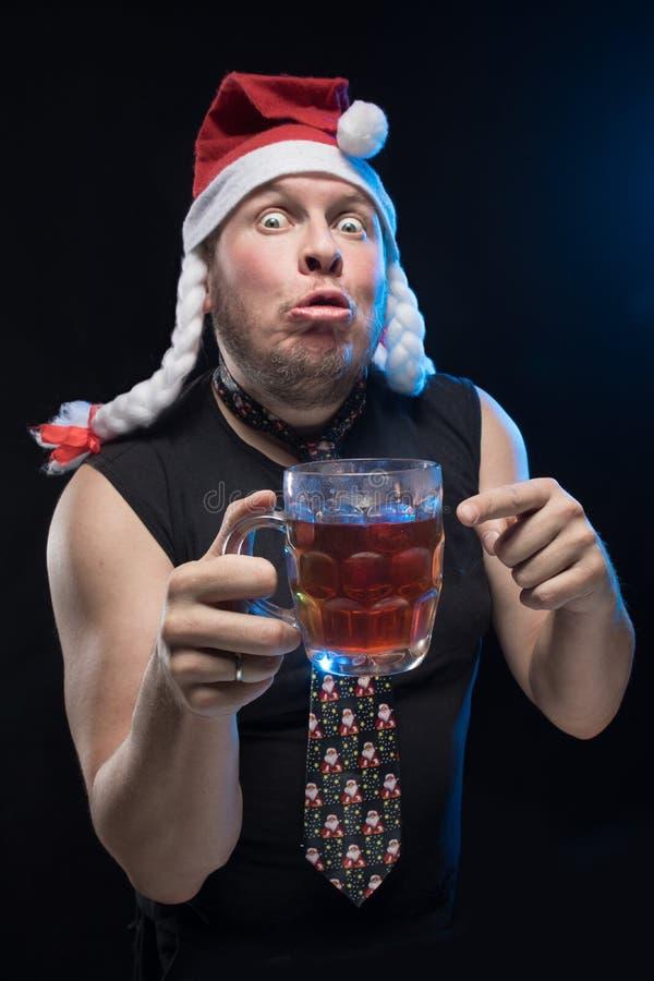 Homem do ator cômico no tampão com tranças com um vidro da cerveja, em antecipação ao Natal e ao ano novo foto de stock