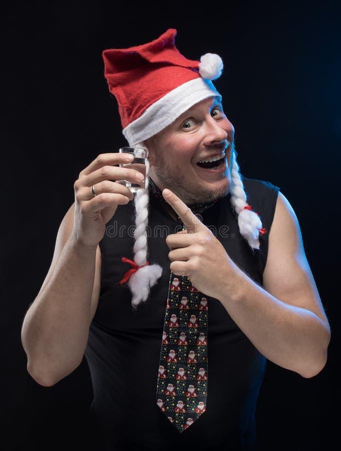 Homem do ator cômico no tampão com tranças com um vidro da vodca, em antecipação ao Natal e ao ano novo fotos de stock