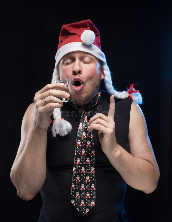 Homem do ator cômico no tampão com tranças com um vidro da vodca, em antecipação ao Natal e ao ano novo fotografia de stock royalty free