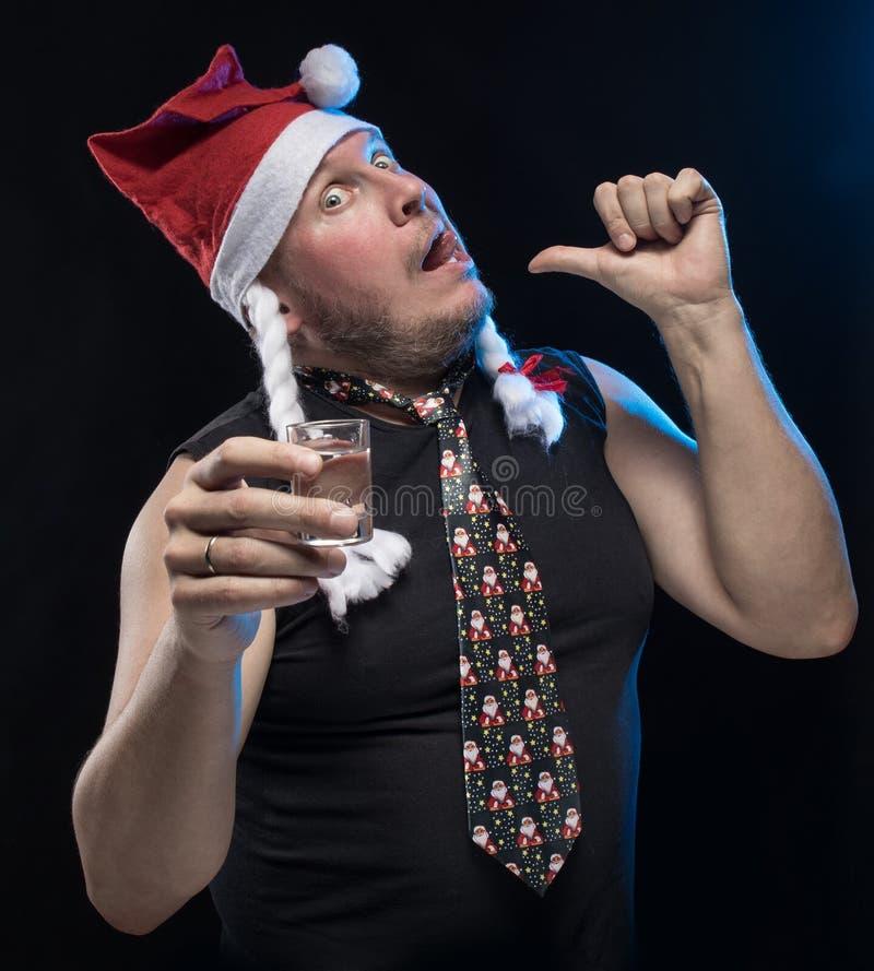 Homem do ator cômico no tampão com tranças com um vidro da vodca, em antecipação ao Natal e ao ano novo imagens de stock royalty free