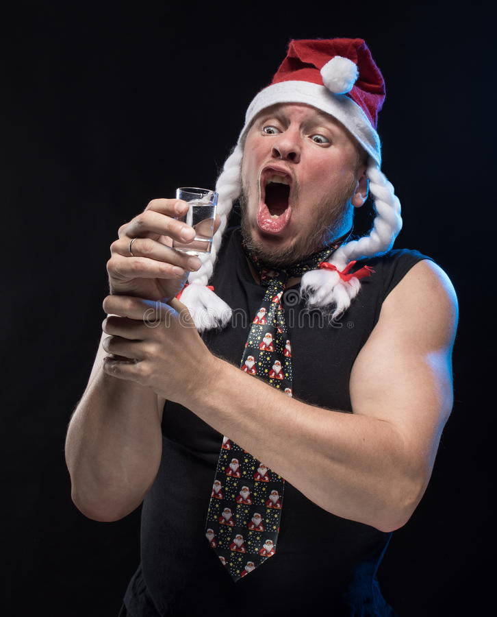 Homem do ator cômico no tampão com tranças com um vidro da vodca, em antecipação ao Natal e ao ano novo foto de stock