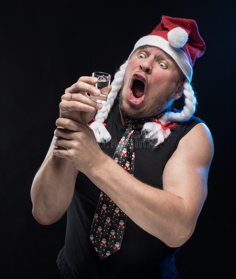 Homem do ator cômico no tampão com tranças com um vidro da vodca, em antecipação ao Natal e ao ano novo imagem de stock royalty free
