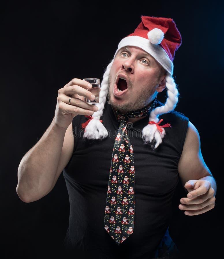 Homem do ator cômico no tampão com tranças com um vidro da vodca, em antecipação ao Natal e ao ano novo fotografia de stock