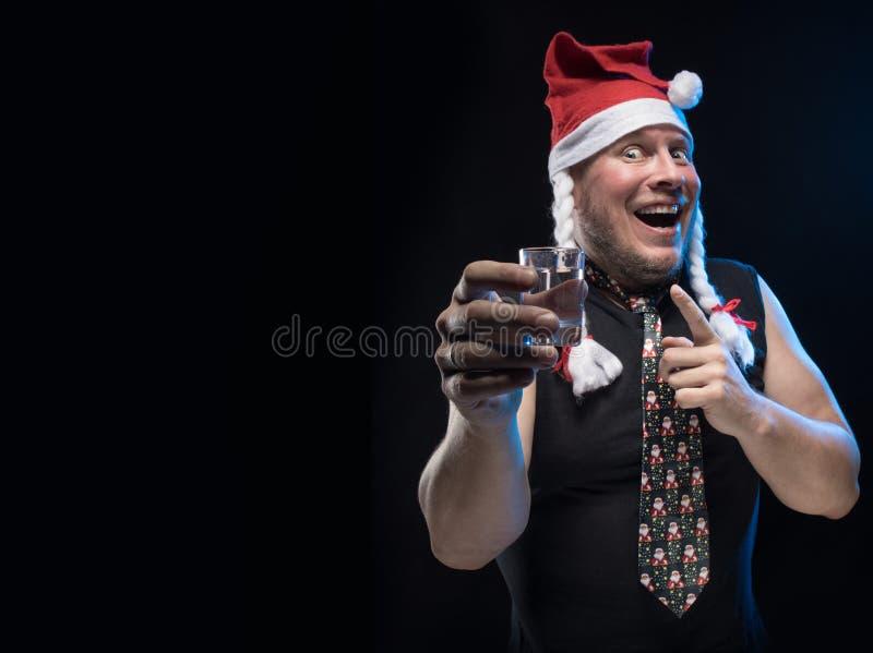 Homem do ator cômico no tampão com tranças com um vidro da vodca, em antecipação ao Natal e ao ano novo imagens de stock