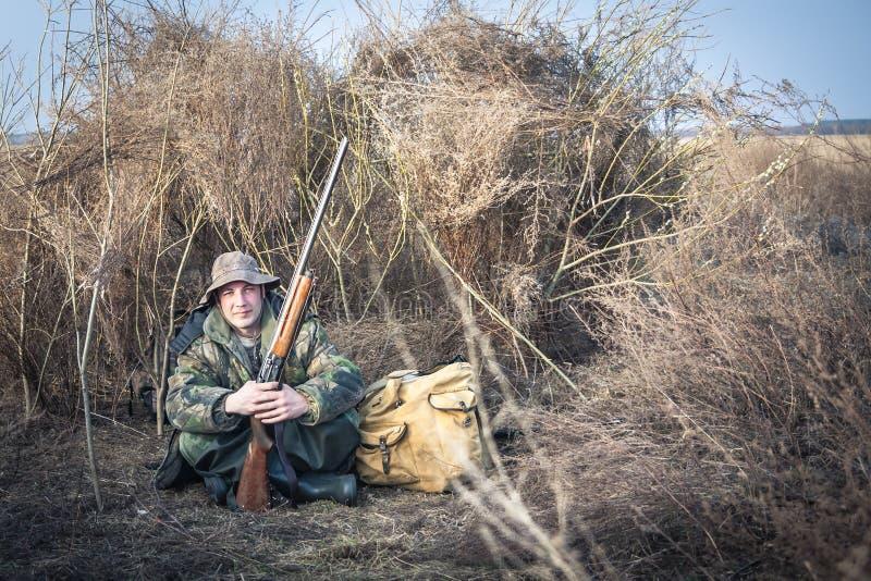 Homem do caçador com a espingarda e a trouxa que têm um resto no campo rural durante a estação da caça foto de stock royalty free