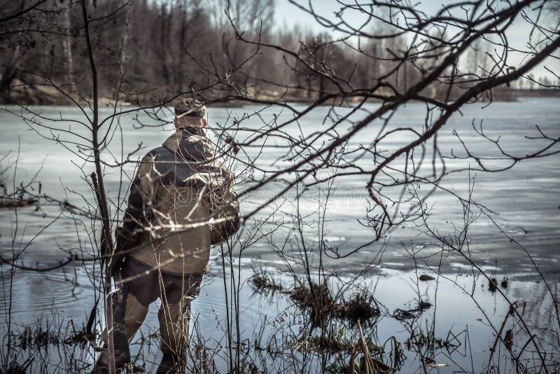 Homem do caçador com a espingarda que está nos arvoredos no rio coberto com o gelo durante a época de caça da mola fotos de stock