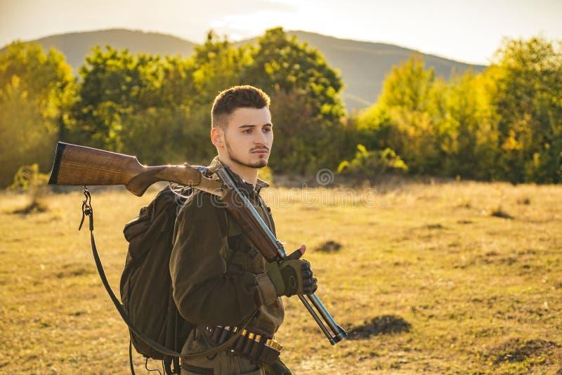 Homem do caçador Caçador com uma trouxa e uma arma de caça Caçando o período, estação do outono Homem com uma arma Um caçador com imagens de stock royalty free