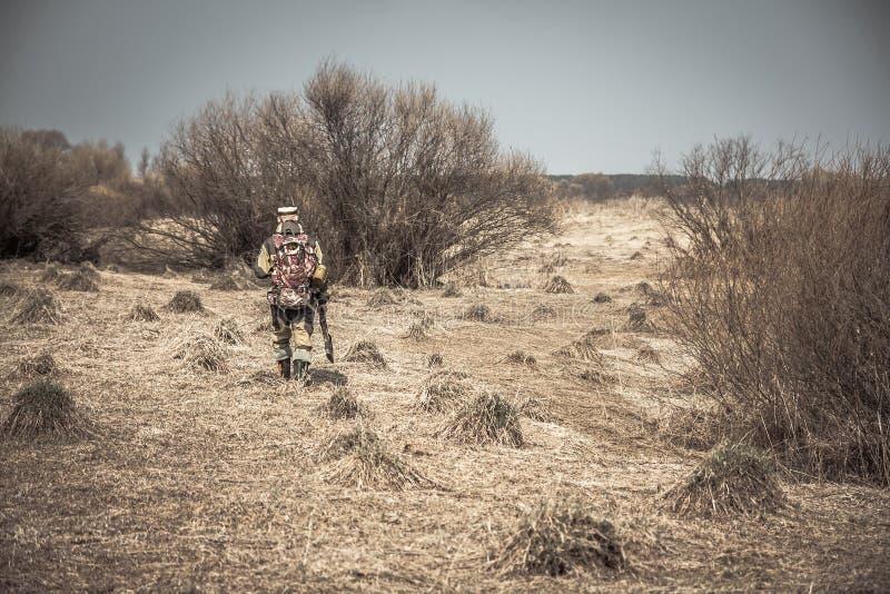 Homem do caçador na camuflagem com a arma que atravessa a área rural com grama seca e arbustos durante a caça fotografia de stock