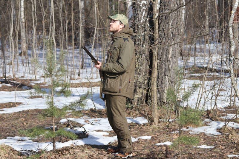 Homem do caçador na roupa caqui escura na floresta foto de stock