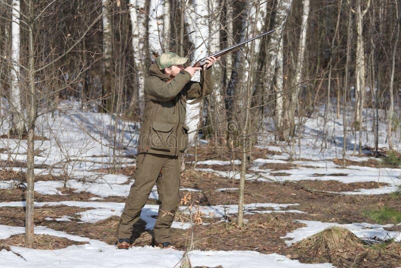Homem do caçador na roupa caqui escura na floresta imagem de stock royalty free