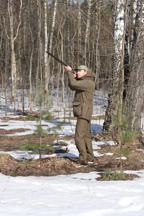 Homem do caçador na roupa caqui escura na floresta fotografia de stock