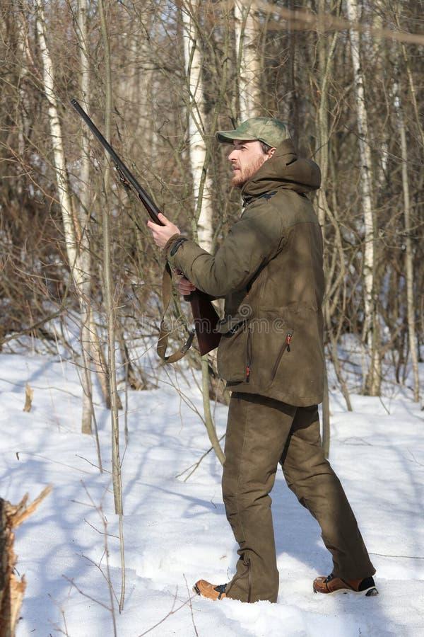 Homem do caçador na roupa caqui escura na floresta imagens de stock royalty free