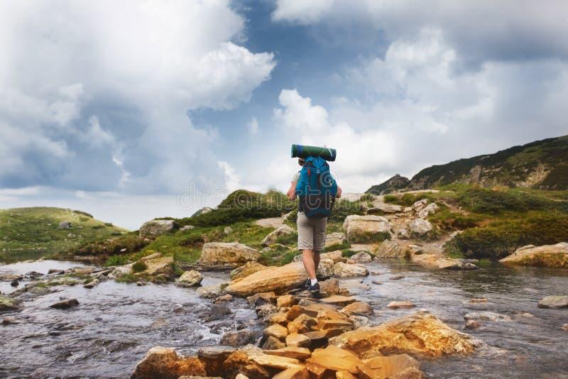 Homem do caminhante com a trouxa que cruza um rio imagens de stock royalty free