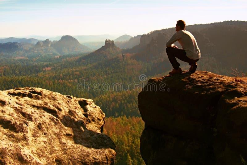 Homem do caminhante do turista no pico da rocha em montanhas rochosas imagens de stock