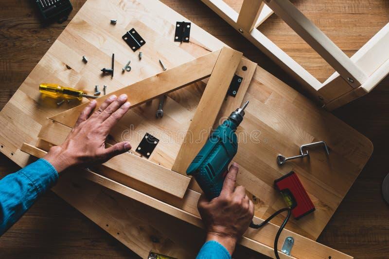 Homem do carpinteiro que trabalha com broca e mobília, fixação ou reparação imagem de stock