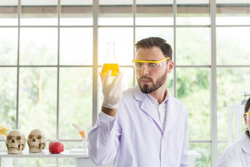 Homem do cientista que trabalha guardando a amostra médica dos produtos químicos na garrafa experimental na sala do laboratório imagens de stock