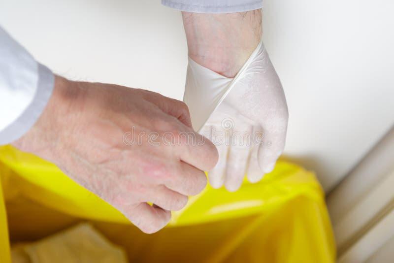 Homem do close-up que remove as luvas do látex das mãos no caixote de lixo imagem de stock royalty free