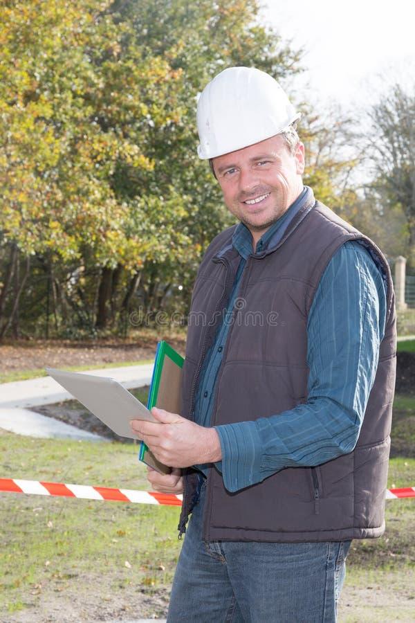 Homem do contratante do trabalhador da construção que usa o laptop da tabuleta foto de stock royalty free