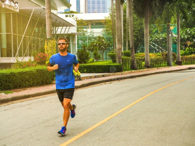 Homem do corredor Conceito exterior da saúde e da aptidão O homem está correndo na manhã e no corredor em um parque fotografia de stock