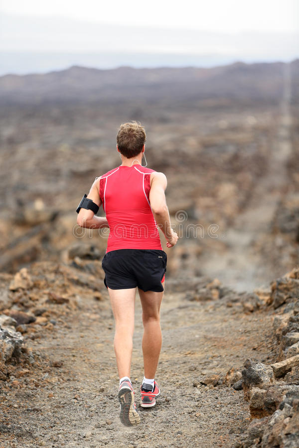 Homem do corredor da fuga que corre a corrida através dos campos imagem de stock